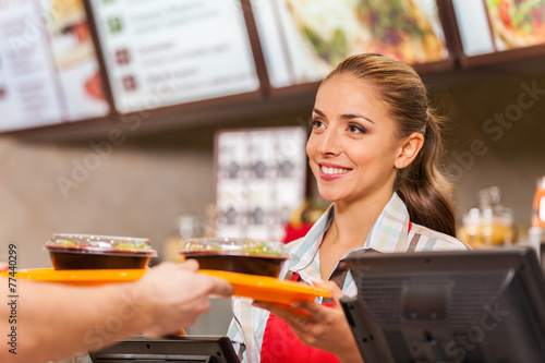 Restaurant worker serving two fast food meals with smile. - 77440299