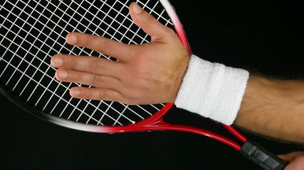 tennis player's hand hitting the net of his tennis racket