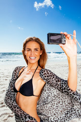 Young woman taking self portrait on the beach