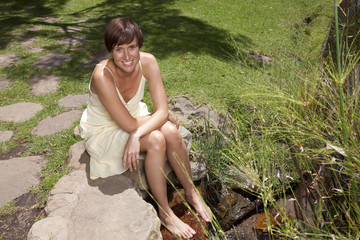 Woman smiling and sitting with feet in stream