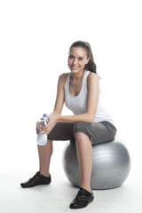 Young woman sitting on fitness ball