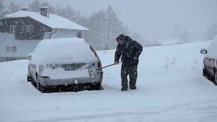 Removing the snow from a car using a broom