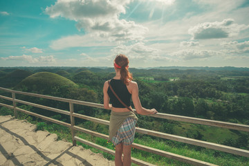Young woman admiring jungle landscape from top of hill