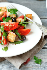 salad with tomatoes and croutons on a white plate