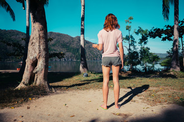Young woman standing by palm trees