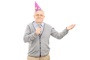 Senior wearing party hat and singing on microphone