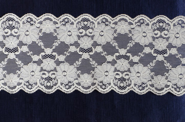 floral lace on the blue silk satin fabric