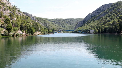 Shot of the river krka with a bridge in front,  made from the moving boat