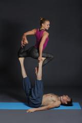 Woman and man doing acro yoga.