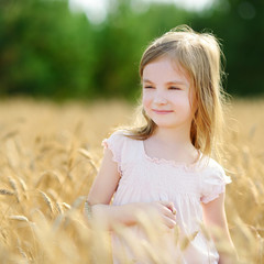 Adorable girl walking happily in wheat field