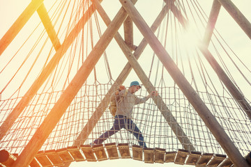 traveling man crossing over hanging bridge in bright sunset
