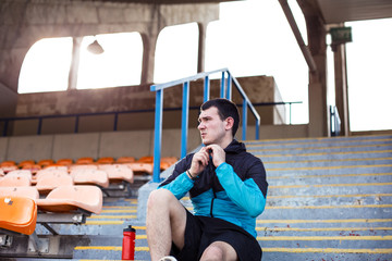 tired sportsman resting with a bottle of water on the stairs