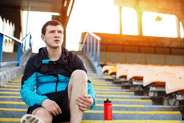 resting sportsman sitting on the stairs holding his leg