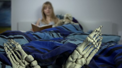 Woman reads in the bed with the skeleton laying beside her