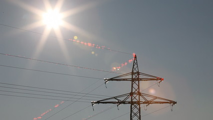 Still shot of sun shining on electricity cables with artificial particles