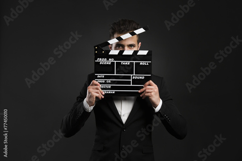 Business man holding a clapboard Poster