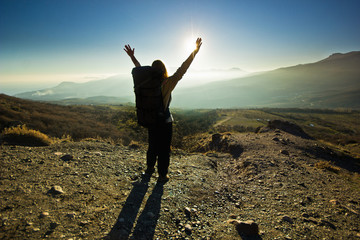 girl-backpacker with hands up in the mountains against sun