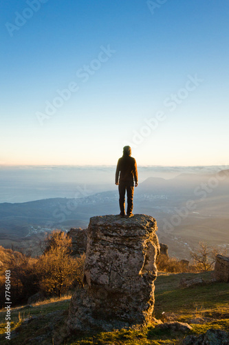 man on the cliff in mountains at sunset - 77450403