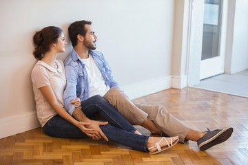 Cute couple sitting on floor against wall