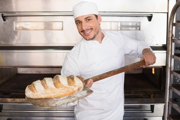 Happy baker taking out fresh loaf