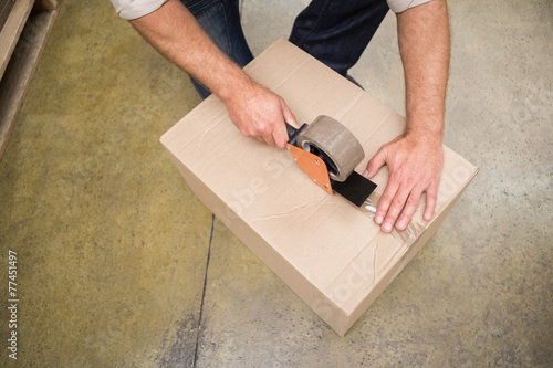 Close up of warehouse worker preparing a shipment - 77451497