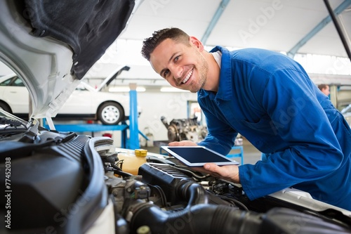 Leinwanddruck Bild Mechanic using tablet on car