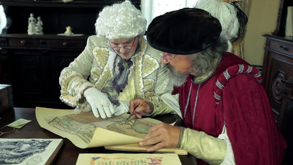 Scholar explaining a map to the mayor of the town