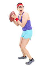 Full length portrait of a young nerdy guy playing football