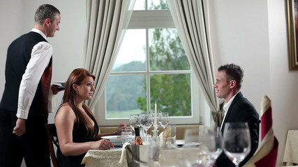 Young couple having romantic lunch inside beautifull restaurant with fancy plate settings and wine