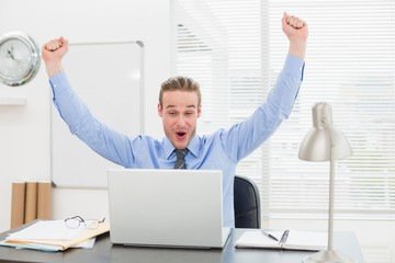 Excited businessman with arms up cheering