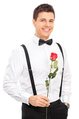 Romantic young guy holding a red rose