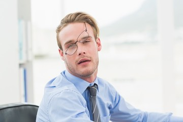 Tired businessman with glasses waking up