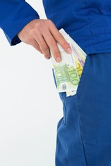 Construction worker putting euro notes in pocket