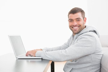 A smiling man using laptop at a table