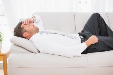 A businessman lying on the sofa at home