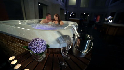decoration with candles, champagne and glasses in front of jacuzzi while young couple having romantic time