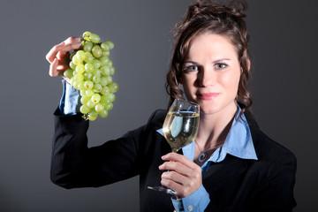 Junge Winzerin zeigt Weißwein und Weintrauben