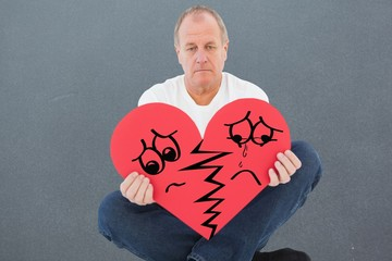 Composite image of upset man sitting holding heart shape