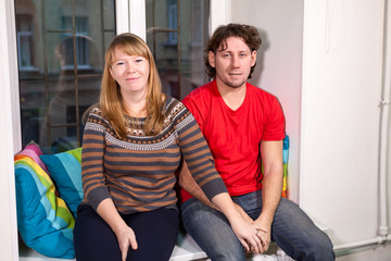 Portrait of Caucasian man and woman sit on window sill together