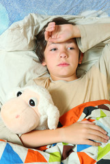handsome preteen boy lay in bed with headache