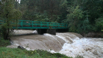 View of the increased restless river runing under the iron bridge