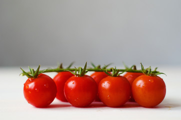 branch of cherry tomatoes on white wooden table