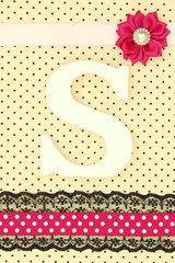 Wooden letter S on polka dots background