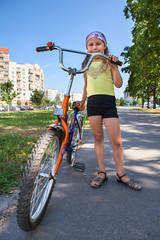 Girl with a bicycle on an asphalt track in the park