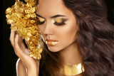 Fototapety Golden makeup eyes closeup. Beautiful young woman in gold with f