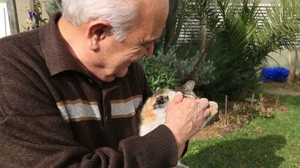 senior man playing cat in garden