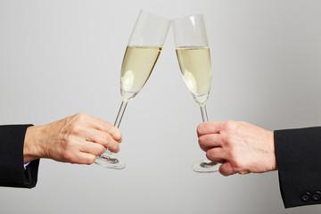 Zwei Hände stoßen mit Sekt im Glas an