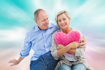 Composite image of happy mature couple with heart pillow