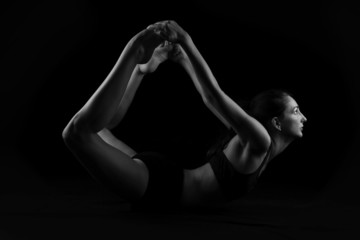 Young woman doing yoga stretches on black background