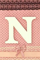Wooden letter N on polka dots background